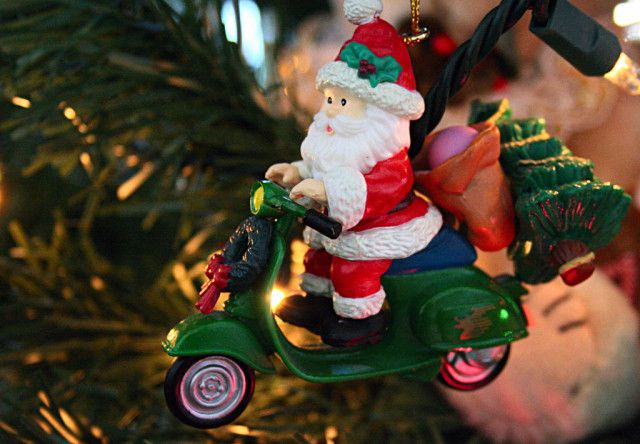 Santa Claus riding a vespa ornament with tree and lights in background