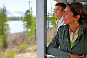 Two guests on outdoor platform of railcar admiring the Alaska scenery
