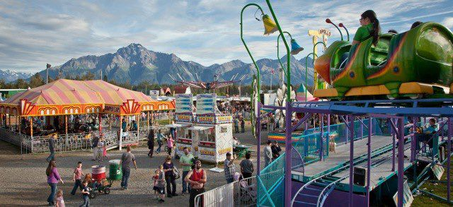 Rides and food vendors at the Alaska State Fair with mountains in the background. Westmark Hotels
