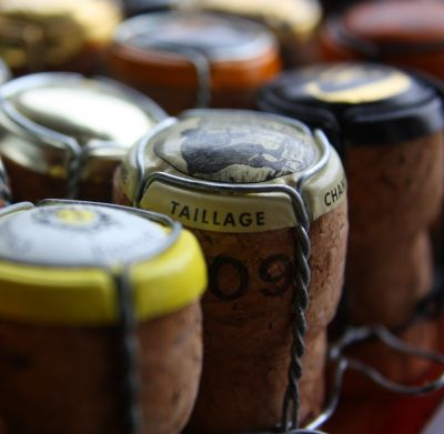 Several bottles of champagne lined up but all you can see is the corks with labels.