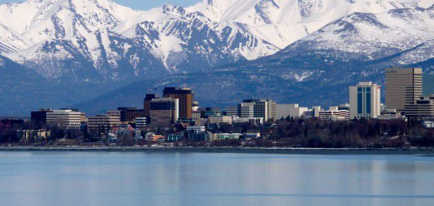 View of Anchorage, AK from across the water with snow-capped mountains in background and skyscrapers in foreground. Westmark Hotels