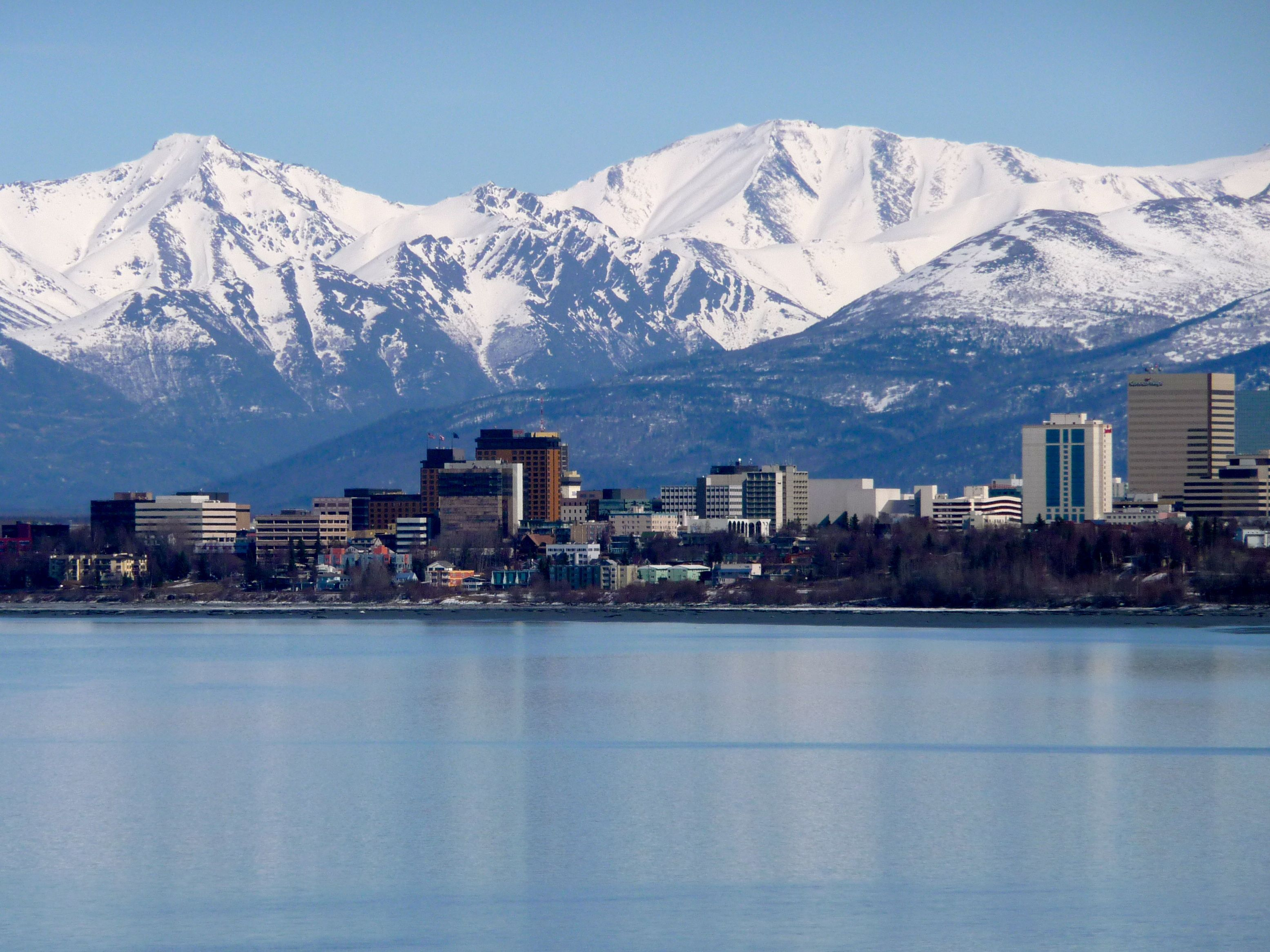 View Of Anchorage Ak From Across The Water With Snow Ced Mountains In Background
