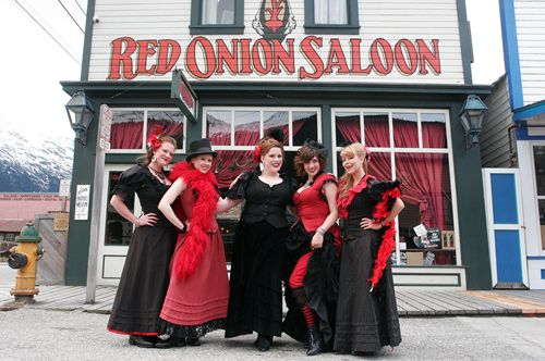 "Five ladies dressed in historical ""madam"" garb stand outside the historic Red Onion Saloon in Skagway, Alaska."