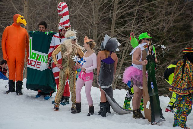 People in an assortment of costumes stand on snow waiting for their chance to partake in the annual Slush Cup