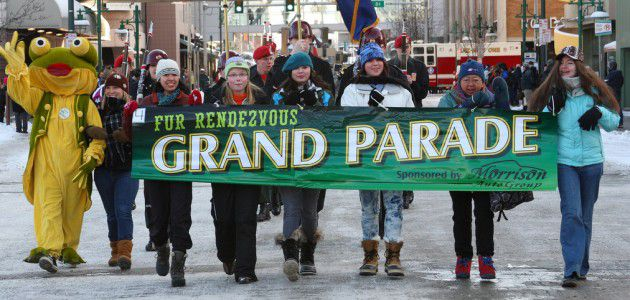 kids holiding a grand parade sign walking down snowy streets