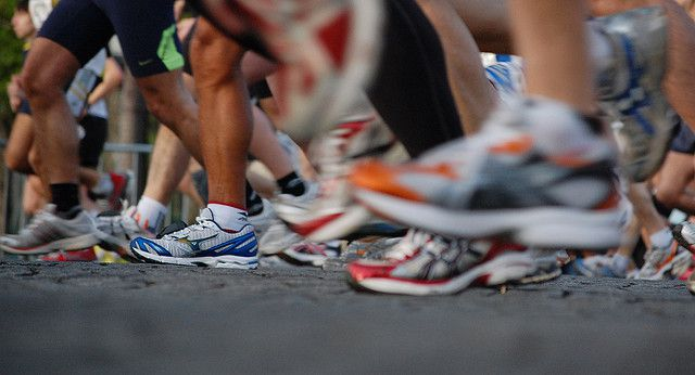 dozens of running shoes hitting the pavement or in motion.