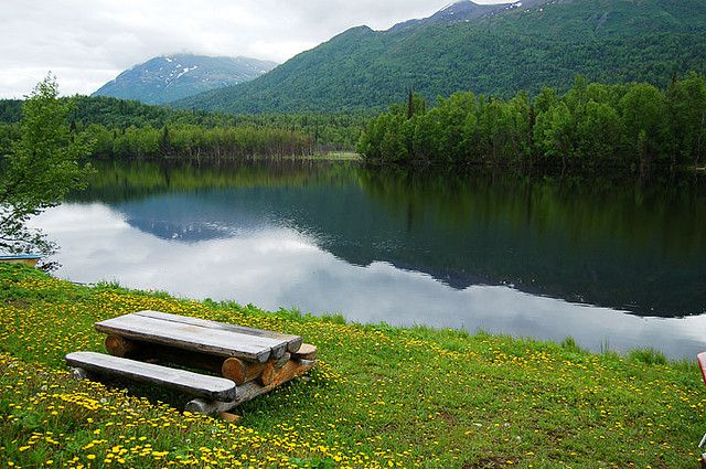 wood picnic bench sits on grass in the foreground while a serene blue lake mirrors a mountain and trees.