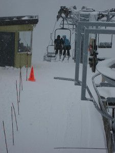 Two people ride the chairlift with snow covering the ground.