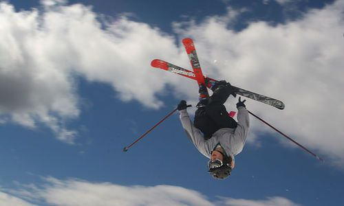 Alpine skiier crosses skis in the air during a jump at a ski mountain, clouds and sky in background.