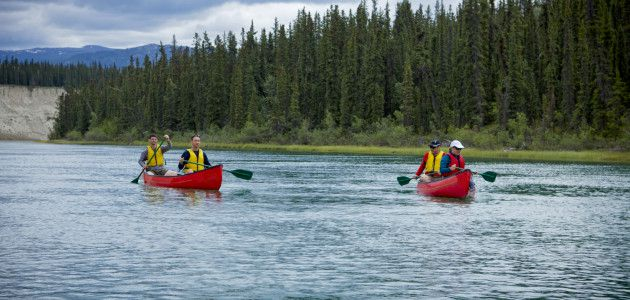 Two canoes that hold two people in each vessel coast down the blue Yukon River with Greenery and the blue sky behind them.