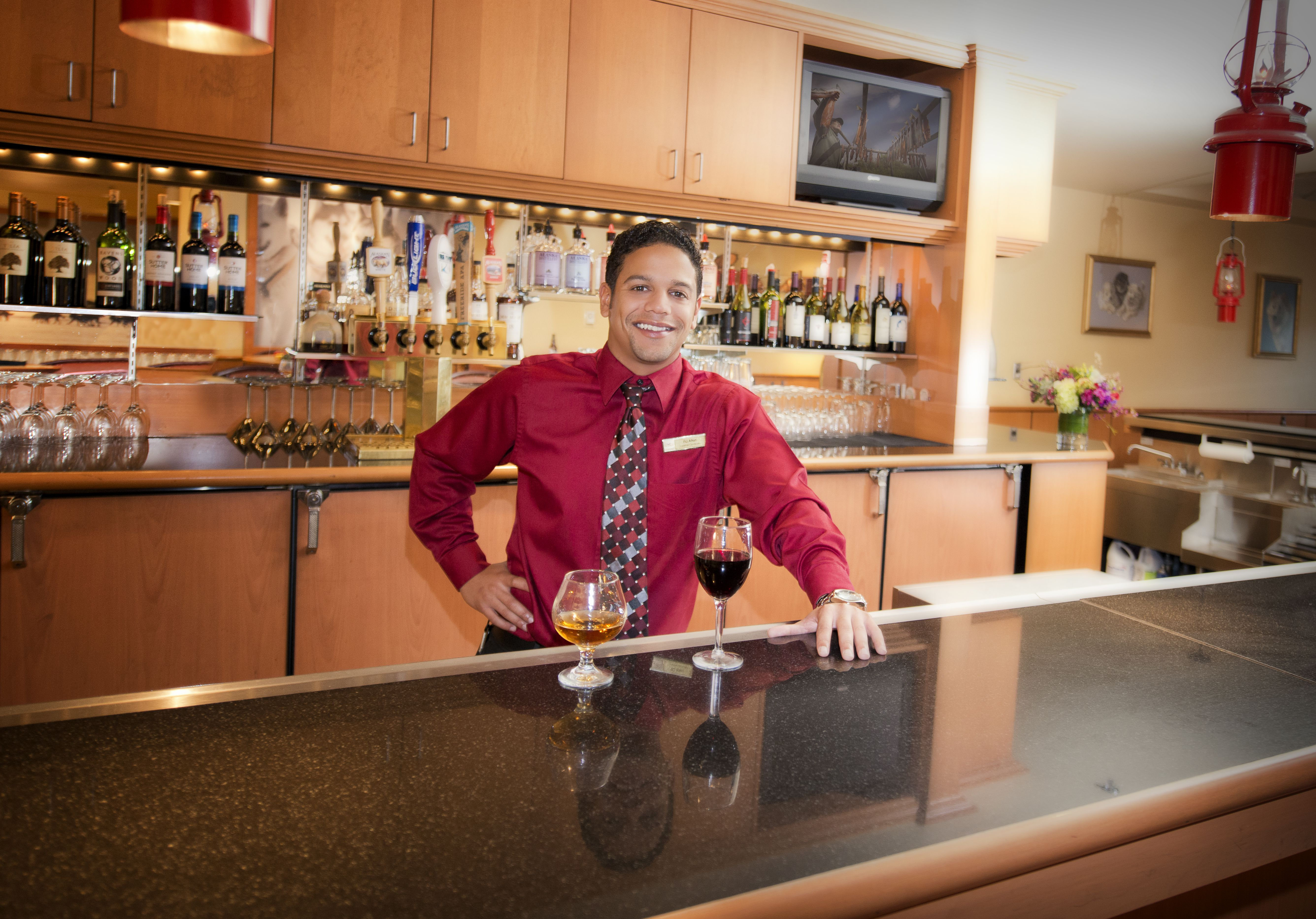 Bartender stands behind a glass of wine and a highball of scotch at the Westmark Fairbanks Hotel and Conference Center
