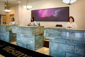 Three hotel reception desks each staffed by a smiling receptionist