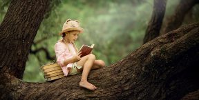 A girl reads a book while sitting in a tree.