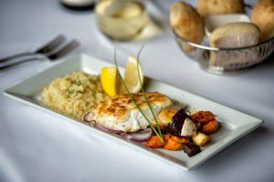 white fish meal with root vegetables and mashed potatoes on a platter with a thyme garnish - Westmark Fairbanks