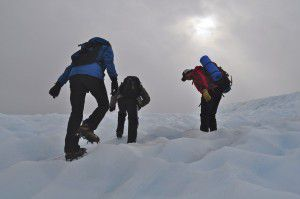 Three hikers in full Winter gear hike Root Glacier with sun poking through the clouds - Westmark Hotels